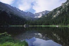 Montagne che riflettono in un lago Fotografie Stock