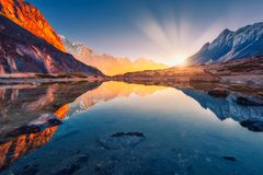 Montagne con i picchi illuminati, pietre nel lago della montagna al sole Immagine Stock Libera da Diritti