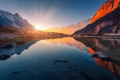 Montagne con i picchi illuminati, pietre nel lago della montagna al tramonto Immagini Stock