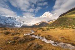 Montagne con i picchi innevati ed il piccolo fiume Fotografia Stock Libera da Diritti