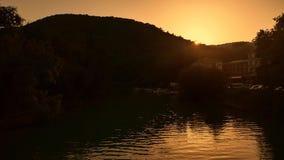 Montagne con la foresta di alba di tramonto di luce solare della siluetta al fondo del ponte e di un fiume su cui yacht e barca stock footage