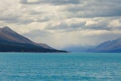 Montagne con le nuvole ed il lago pesanti Pukaki sulla priorità alta, Nuova Zelanda, isola del sud, Canterbury Immagine Stock Libera da Diritti