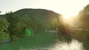 Montagne con una foresta verde al fondo del ponte e di un fiume su cui gli yacht ed i crogioli di barca galleggiano nave video d archivio