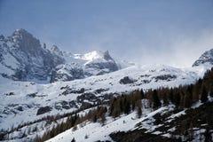 Montagne coperte di neve, di cielo blu con le nuvole e di foresta di inverno vicino a Mont Blanc Alpes, Italia Immagini Stock