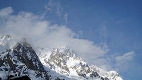 Montagne coperte di neve, di cielo blu con le nuvole e di foresta di inverno vicino a Mont Blanc Alpes, Italia Fotografie Stock