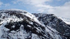 Montagne coperte di neve, di cielo blu con le nuvole e di foresta di inverno vicino a Mont Blanc Alpes, Italia Fotografia Stock