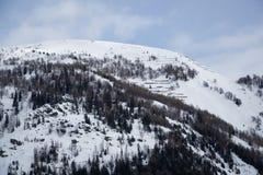 Montagne coperte di neve, di cielo blu con le nuvole e di foresta di inverno vicino a Mont Blanc Alpes, Italia Fotografia Stock Libera da Diritti