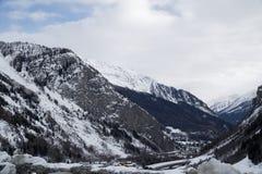 Montagne coperte di neve, di cielo blu con le nuvole e di foresta di inverno vicino a Mont Blanc Alpes, Italia Immagine Stock