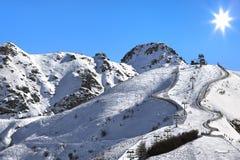 Montagne coperte di neve sotto cielo blu. Immagine Stock