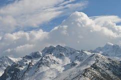 Montagne coperte in neve di nuvole nel fondo Immagini Stock