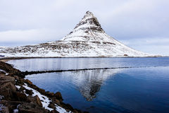 Montagne couronnée de neige de Kirkjufell avec la réflexion sur le lac Photos stock