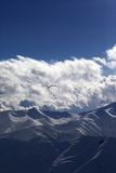 Montagne d'hiver dans la soirée et la silhouette du parachutiste Photo stock
