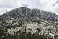 Montagne de granit se levant au-dessus de la forêt photos stock