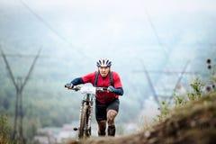 Montagne de montée de mountainbiker d'homme à pied avec leur bicyclette Image stock