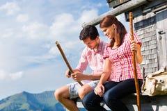 Montagne dell'alpe - uomo e donna che si siedono alla cabina Fotografie Stock Libere da Diritti