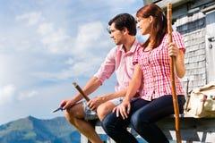 Montagne dell'alpe - uomo e donna che si siedono alla cabina Fotografia Stock