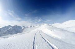 Montagne della neve con la strada fotografia stock