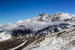 Montagne della neve delle alpi con le nuvole e la nebbia Fotografie Stock