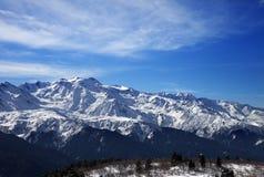 Montagne della neve di luce solare e cielo nuvoloso nel giorno di inverno del vento Fotografia Stock