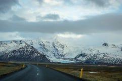 Montagne della neve e strade principali islandesi immagini stock libere da diritti