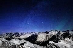 Montagne delle alpi alla notte, picchi nevosi di una catena montuosa sotto un grande cielo stellato Immagini Stock