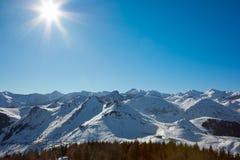 Montagne delle alpi con neve in inverno, sole e cielo blu Immagine Stock