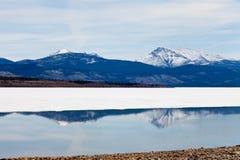 Montagne dello Snowy rispecchiate sul lago Laberge, Yukon immagini stock libere da diritti