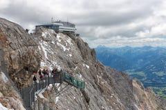 Montagne di Dachstein dell'austriaco con le viandanti che passano un ponte di corda dello skywalk Immagini Stock
