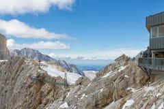 Montagne di Dachstein dell'austriaco con le viandanti che passano un ponte dello skywalk Fotografie Stock