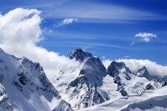 Montagne di inverno con il cornicione della neve e cielo blu con le nuvole nella n Immagini Stock