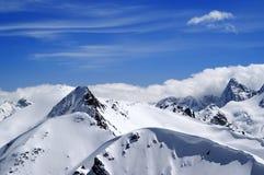 Montagne di inverno con il cornicione della neve e cielo blu con le nuvole nella n Fotografia Stock