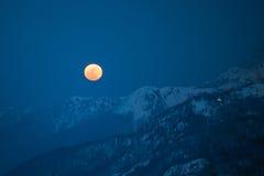 Montagne di inverno con la luna Fotografie Stock Libere da Diritti