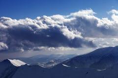 Montagne di inverno in nuvole di luce solare e di sera Fotografia Stock
