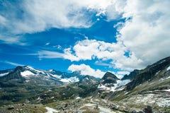 Montagne di paesaggio delle alpi davanti a cielo blu Immagine Stock