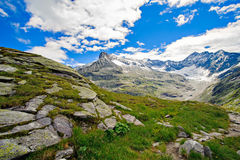 Montagne di paesaggio delle alpi davanti a cielo blu Fotografia Stock