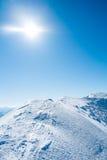 Montagne di Snowy con il sole Immagine Stock