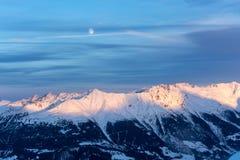 Montagne di Snowy durante il tramonto nelle alpi con l'Abo della luna piena Immagine Stock Libera da Diritti