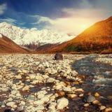 Montagne di Snowy e fiume rumoroso della montagna al tramonto Fotografia Stock Libera da Diritti