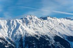 Montagne di Snowy nelle alpi con sole Immagini Stock Libere da Diritti