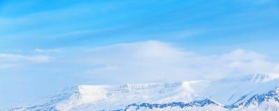 Montagne di Snowy sotto il cielo nuvoloso blu Fotografia Stock