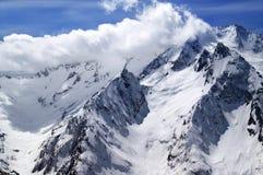 Montagne e cielo blu della neve di inverno con le nuvole nel giorno piacevole del sole Immagine Stock Libera da Diritti