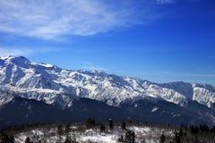 Montagne e cielo blu della neve di luce solare con le nuvole nel giorno di inverno Fotografia Stock
