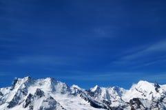 Montagne e cielo blu nevosi di inverno nel giorno soleggiato freddo Immagini Stock Libere da Diritti