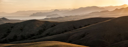 Montagne e colline accese dal sole Fotografia Stock