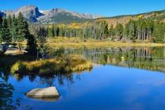 Montagne e lago alpino con la riflessione nella caduta Immagini Stock