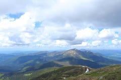 Montagne e nuvole stupefacenti delle alpi nel fondo Immagini Stock Libere da Diritti