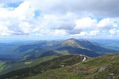 Montagne e nuvole verdi stupefacenti delle alpi nel fondo Immagine Stock Libera da Diritti