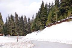 Montagne e strada principale nevicate Immagine Stock Libera da Diritti