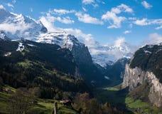 Montagne e valle verde ricoperte neve Immagini Stock Libere da Diritti