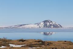 Montagne et réflexion au-dessus du lac avec le fond clair de ciel bleu, Islande Photo stock